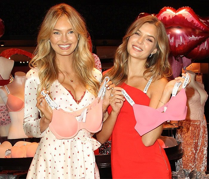 Romee Strijd and Josephine Skriver showing off two pink logo-ribbon-strapped Victoria's Secret bras.