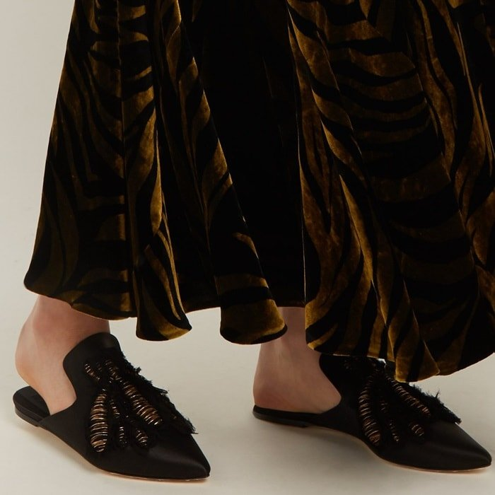 Theseblack satin 'Ragno' slipper shoes are embroidered in Italy with a bronze bee motif and edged with frayed crepe to heighten the handmade feel.