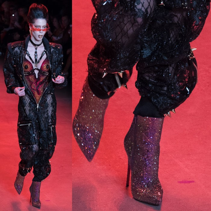 A model wearing Christian Louboutin for The Blonds glitter booties with a crystal bodysuit and a spiked mesh zip jumpsuit.