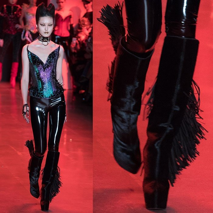 A model wearing a shimmery, reptilian-scale corset with Christian Louboutin for The Blonds black fringed slouchy platform boots.