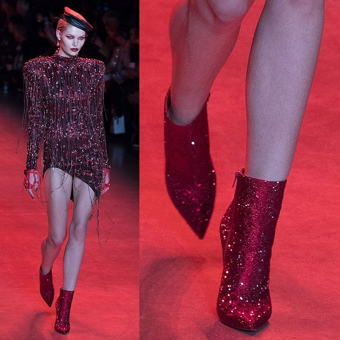 A model wearing Christian Louboutin for The Blonds red glitter ankle boots.
