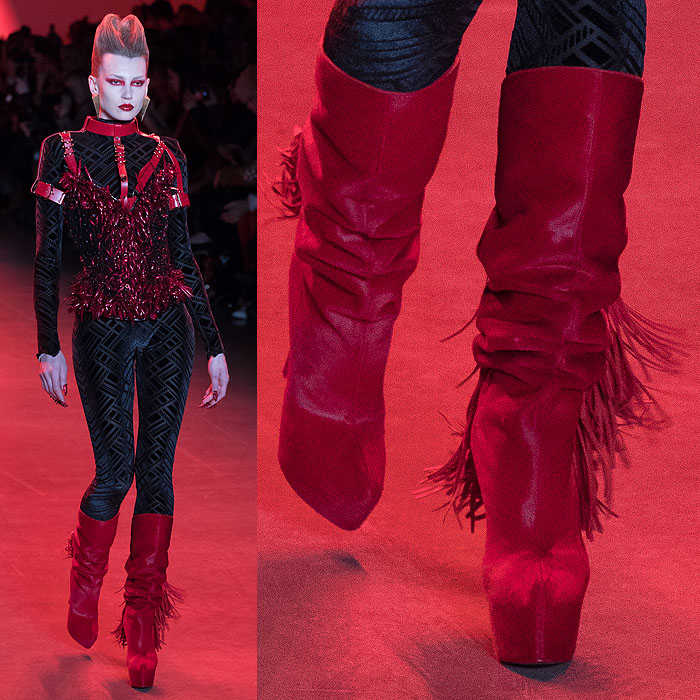 A model wearing red fringed slouchy boots with a red, leather-harnessed corset covered in glittery red talons.