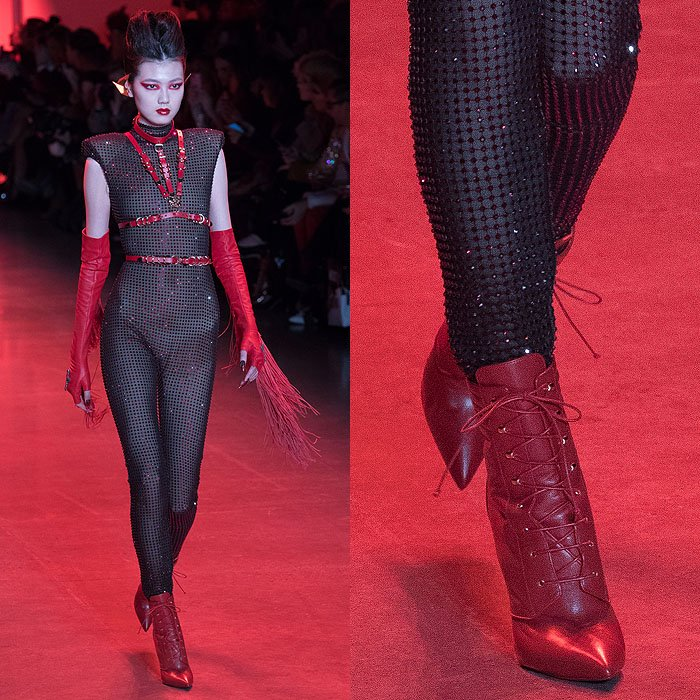 A model wearing a crystal-mesh bodysuit with a red leather harness, fringed fingerless gloves, and Christian Louboutin for The Blonds red leather lace-up booties.