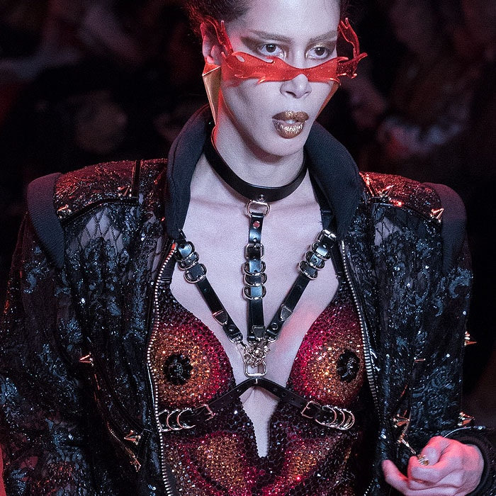 Model wearing flame sunglasses, a black leather harness, a multicolor-crystal bodysuit, and a spiked black zip jumpsuit at The Blonds Fall 2018 fashion show.