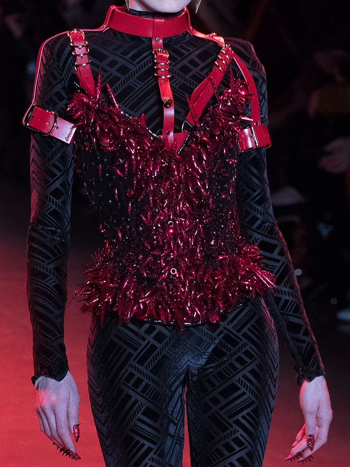 Glittery red-spiked corset and matching nails.