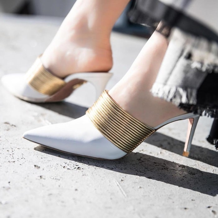 These mules are detailed with the same fine metallic strips as those seen on the label's coveted 'Spin Me Around' sandals