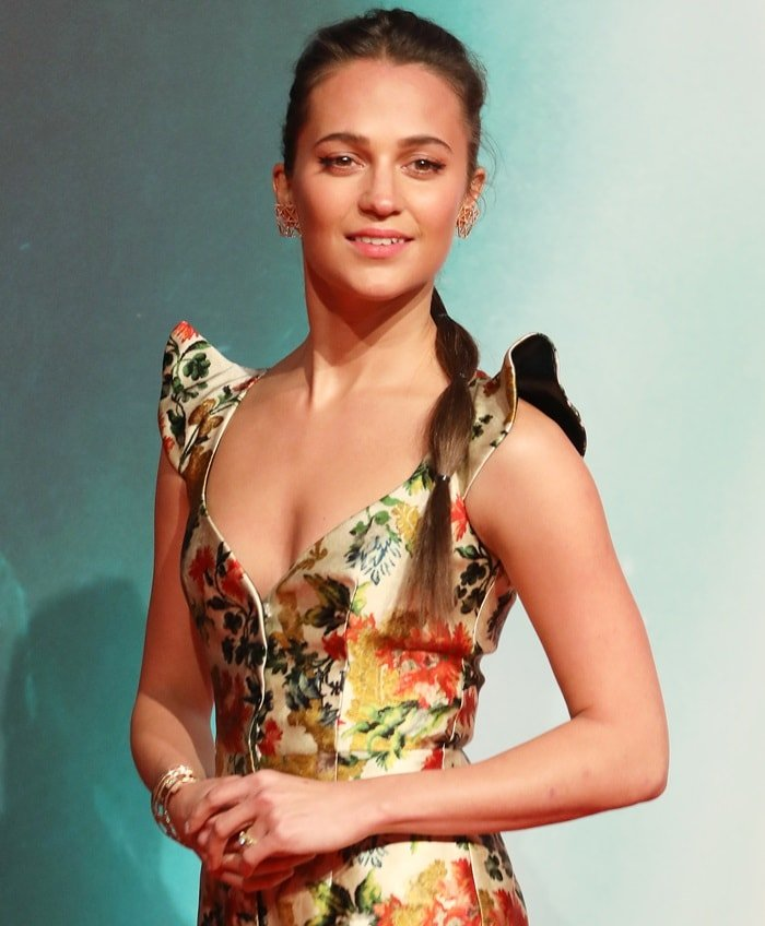 Alicia Vikander'sside parted braided hairstyle and berry lip