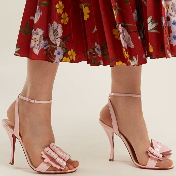 Christian Louboutin's iconic bows are reinterpreted with a modern twist in the form of the laser-cut strips on these baby-pink Miss Valois sandals