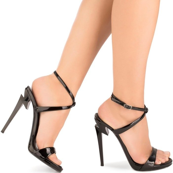Made in Italy from black patent leather, these sandals feature an open toe, an ankle strap with a side buckle fastening, a branded insole, and a sculpted high stiletto heel