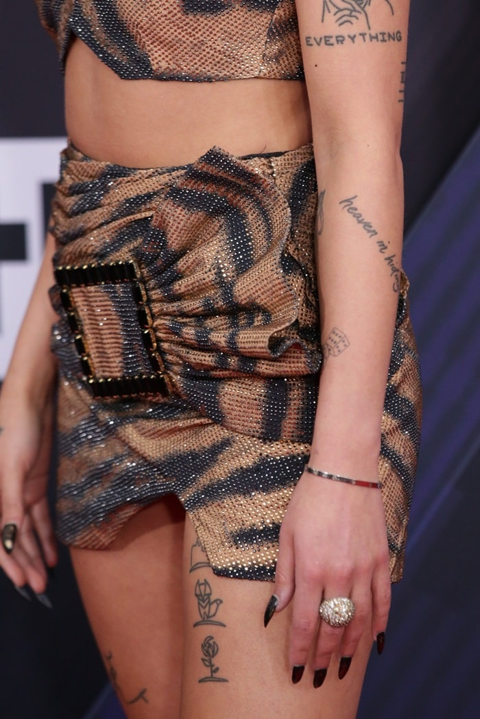 Halsey's numerous tattoos, glittering ring, and black manicure