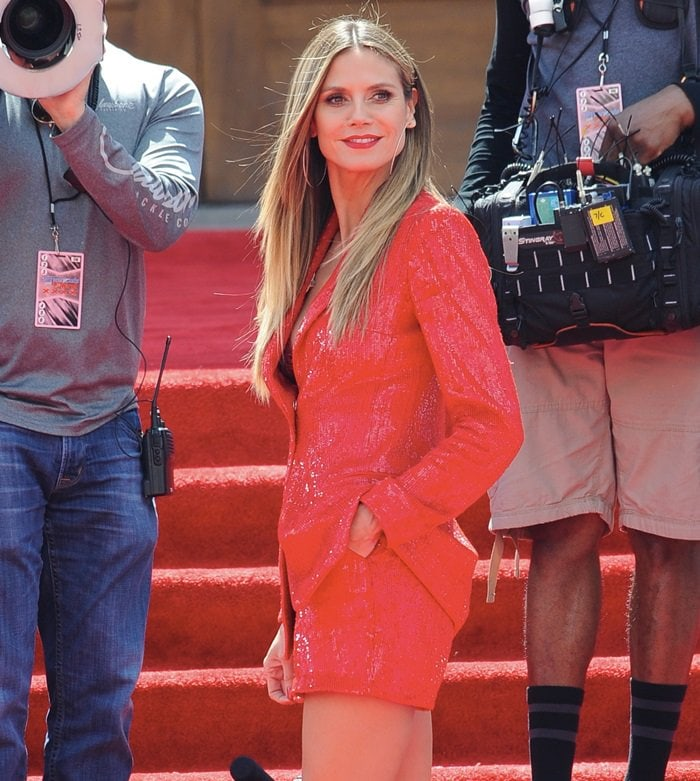 Heidi Klum hits the red carpet in a red tight red sequined look from the Rasario Spring 2018 collection