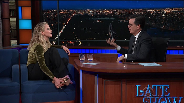 Jennifer Lawrence and Stephen Colbert kicking off their shoes.
