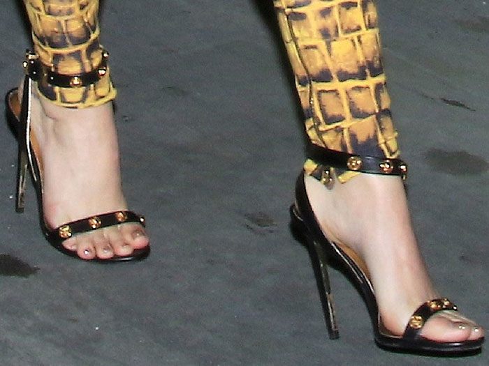 Katy Perry's feet in black leather ankle-strap sandals with gold Medusa medallions