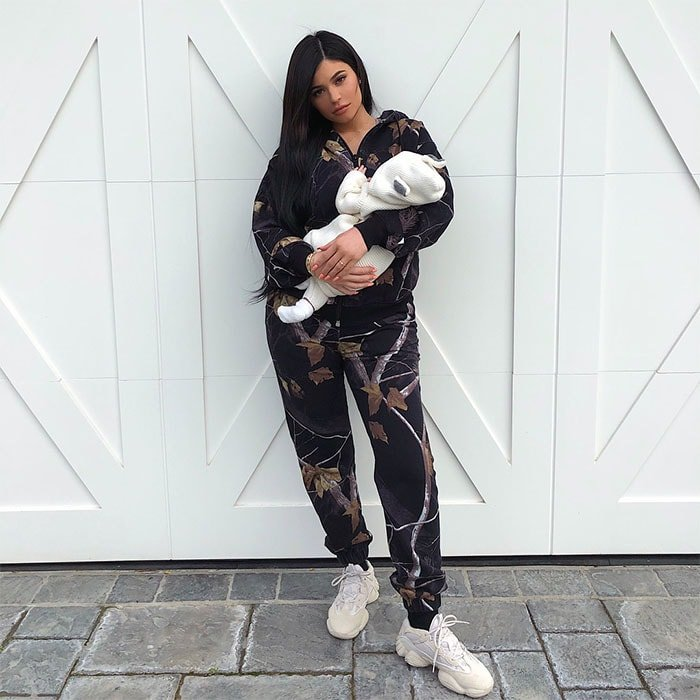 Kylie Jenner in Yeezy 'Desert Rat 500' sneakers holding her one-month old baby Stormi.