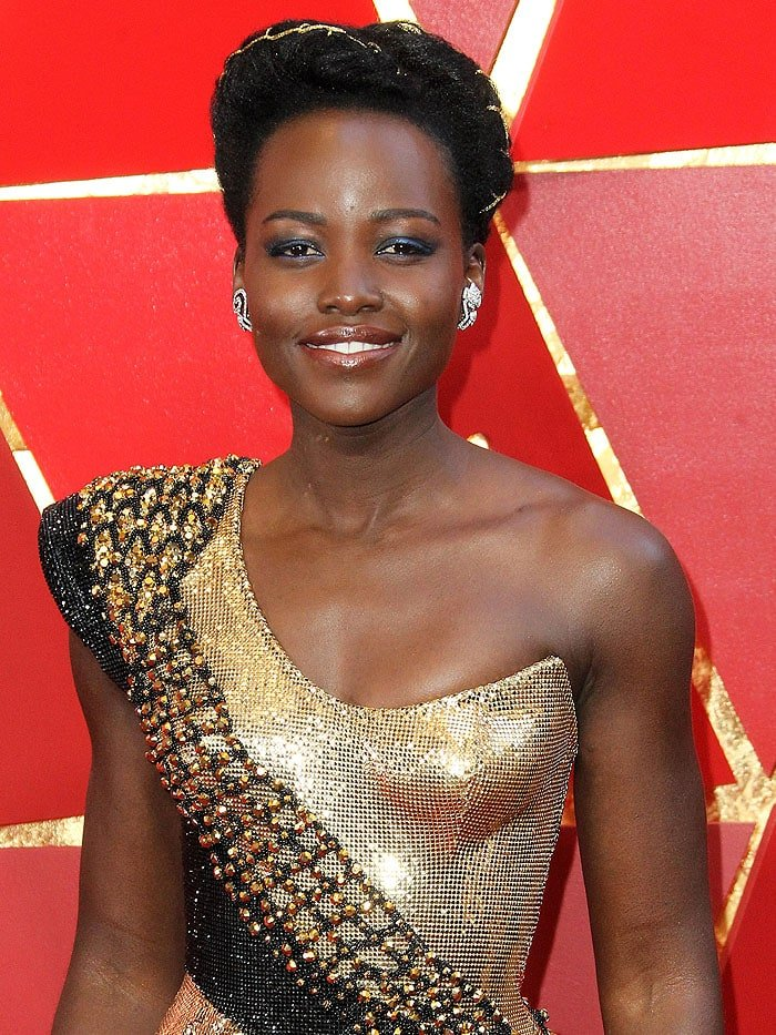Lupita Nyong'o with a gold string braided through her twisted hairdo at the 2018 Oscars.