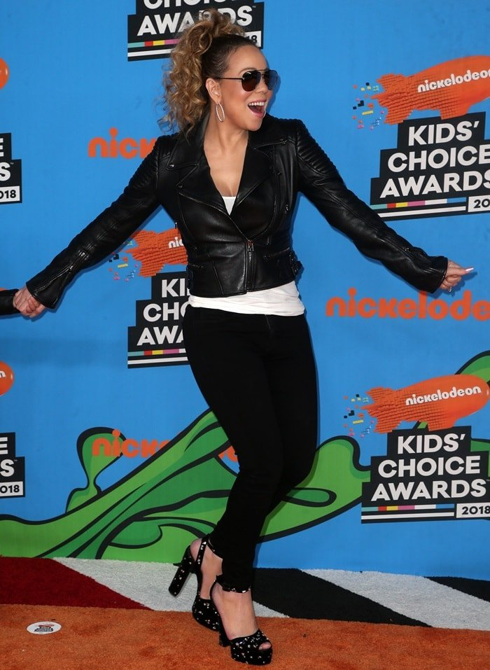 Mariah Carey styled her Tom Ford jacket with hoop earrings, tight jeans, and bejeweled peep-toe platform sandals