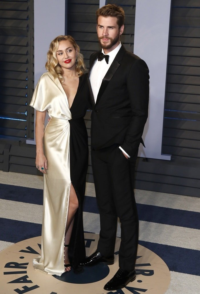 Miley Cyrus ina black and ivory silk crepe back satin v-neck column gown