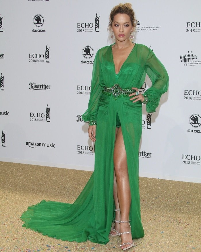 Rita Ora wearing a custom green Versace gown featuring a plunging neckline