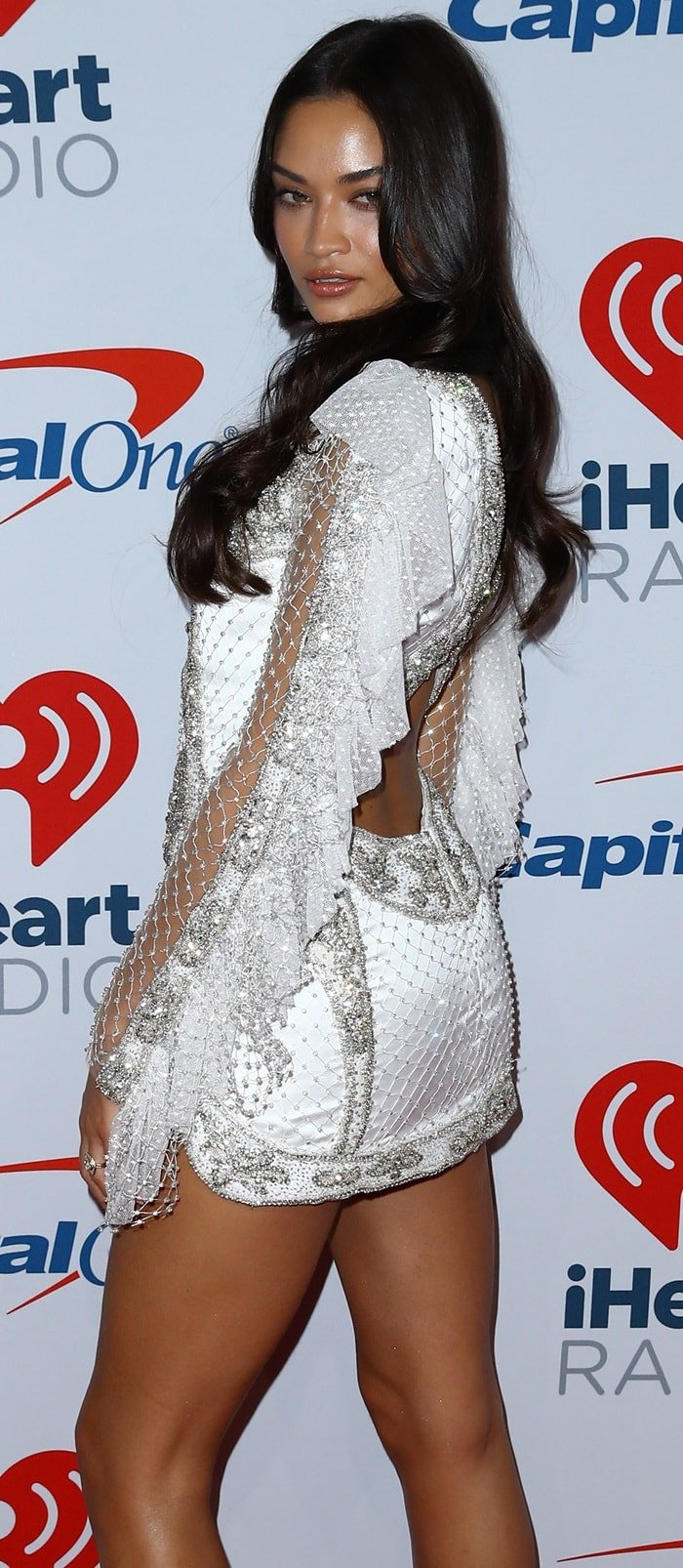 Shanina Shaik wearing a dazzling beaded dress featuring sheer sleeves and an exposed lower back