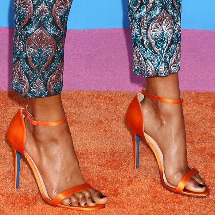 Skai Jackson's feet in pineapple-orange satin ankle strap Loriblu sandals with a thin heel