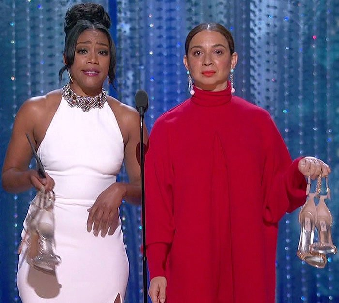 Tiffany Haddish and Maya Rudolph with their shoes in their hands while presenting at the 2018 Oscars.