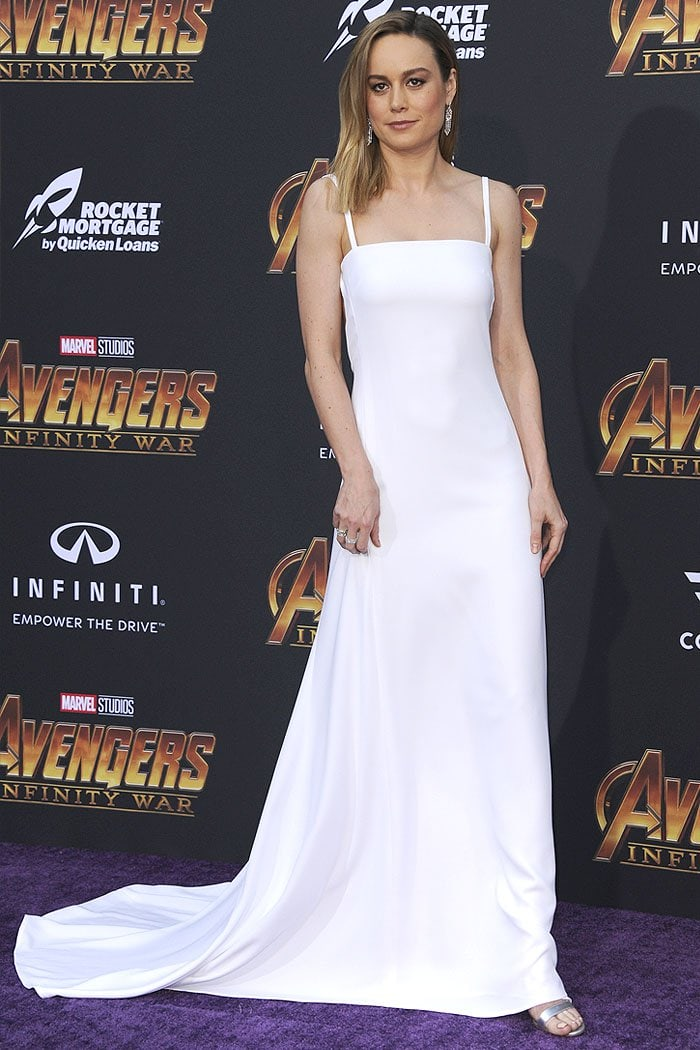 Brie Larson in a Carolina Herrera Spring 2019 open-back bridal gown and silver ankle-strap sandals.
