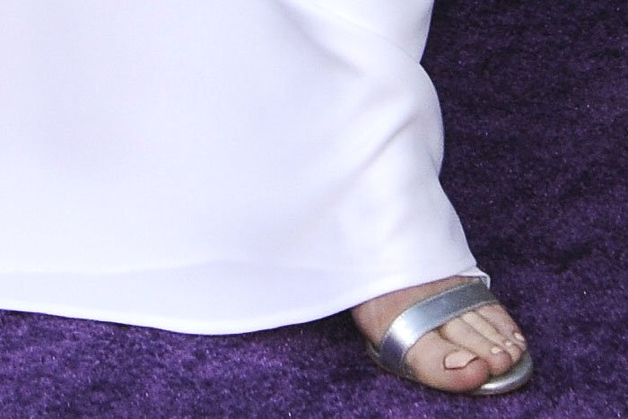 Closeup of Brie Larson's Manolo Blahnik 'Chaos' sandals in silver leather.