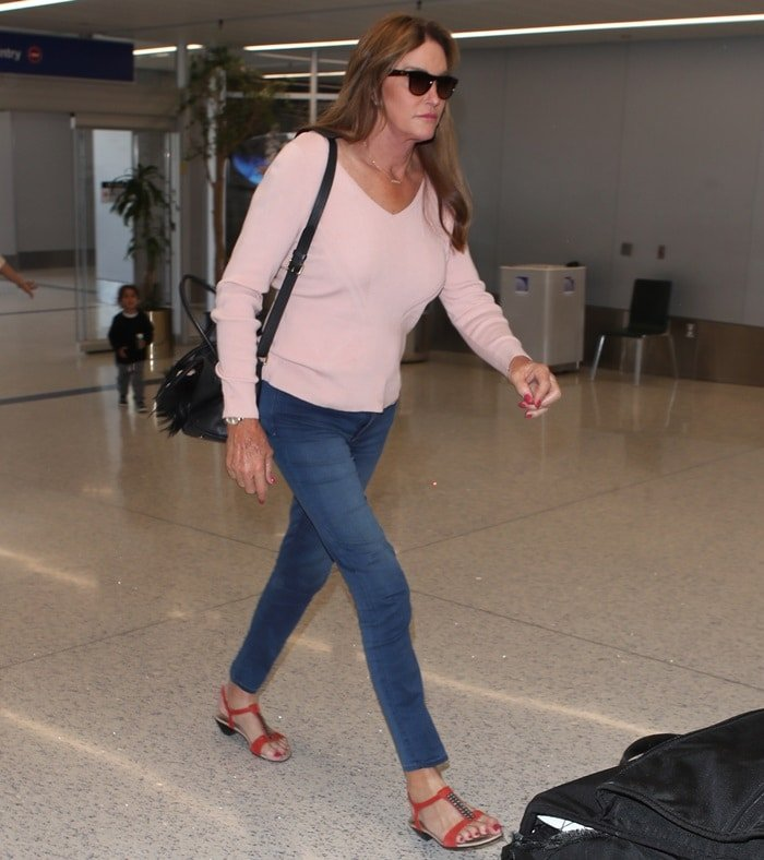 Caitlyn Jenner wearing a pale pink sweater paired with large dark sunglasses and skinny jeans