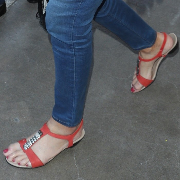 Caitlyn Jenner showing off her red pedicure in orange sandals