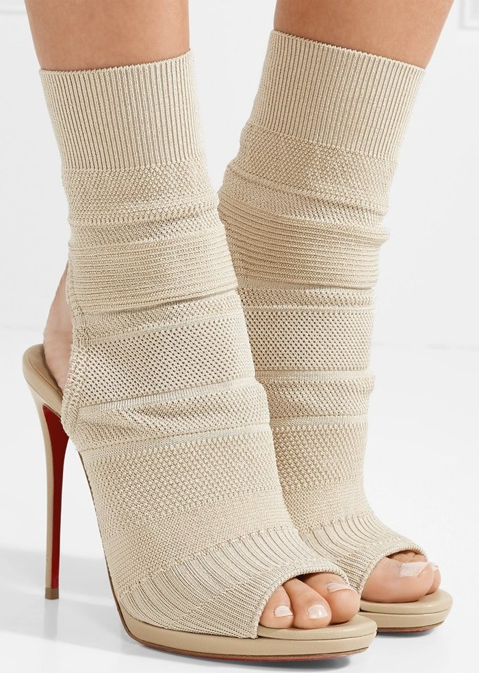 Bands of ribbing and pebbling ladder up the knit sock upper of a multi-textured sandal lofted high on an impossibly slender stiletto