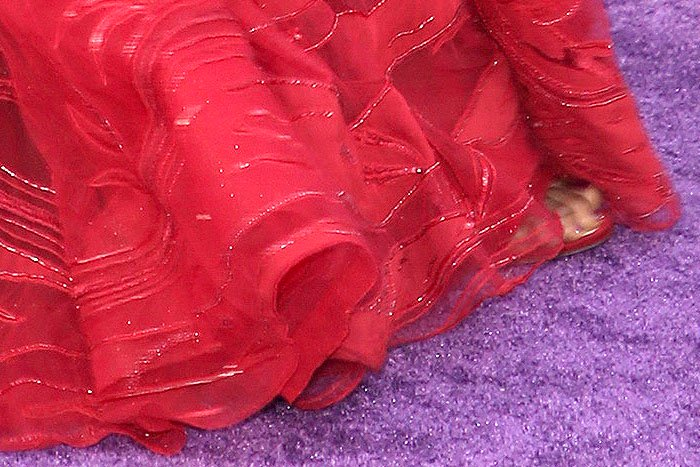 Glittery, red Jimmy Choo sandals peeking out from underneath Danai Gurira's red Zuhair Murad gown.