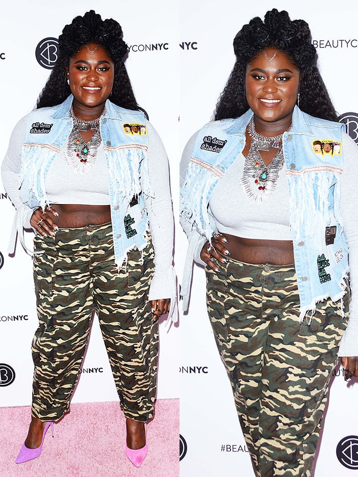 Danielle Brooks in a patched denim vest, a gray crop top, camo pants, and mismatched pink and purple pumps at BeautyCon 2018.