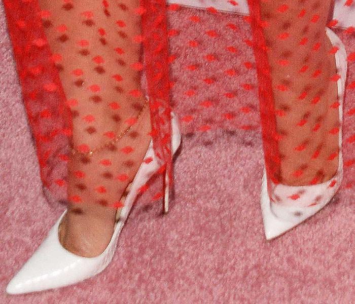 Closeup of the Christian Louboutin 'So Kate' pumps in white python on Dascha Polanco.
