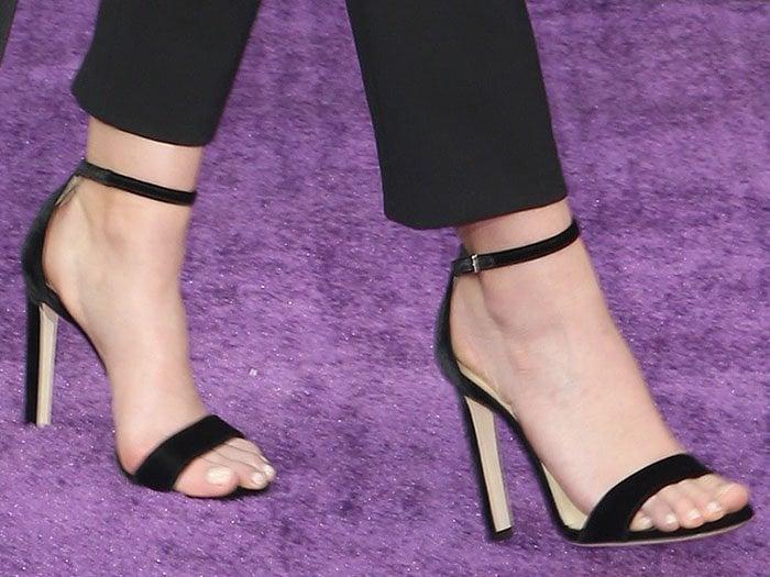 Closeup of the Jimmy Choo black-velvet ankle-strap sandals on Elizabeth Olsen.