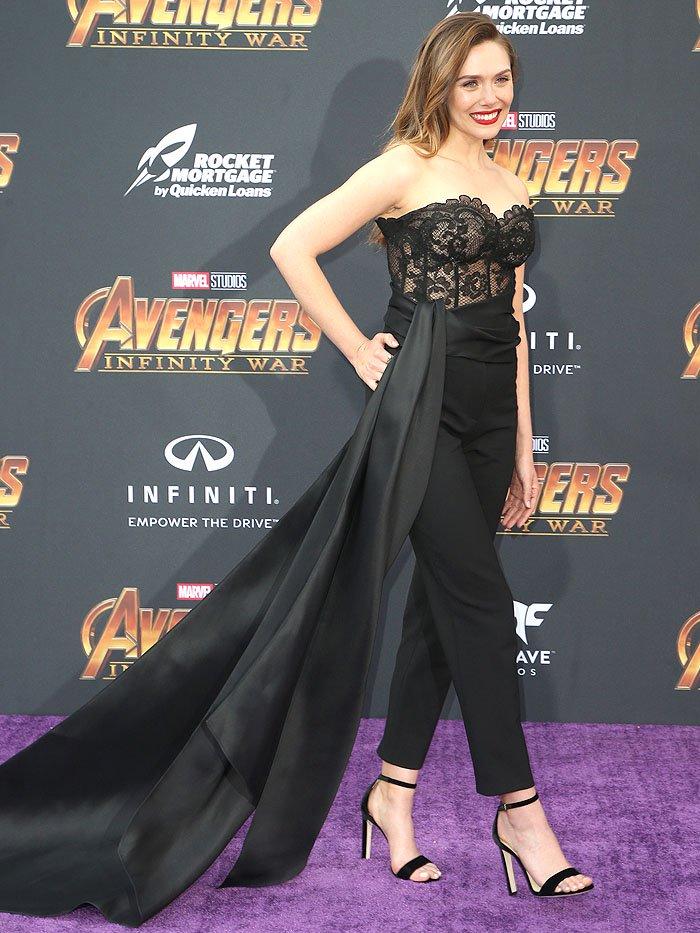 Elizabeth Olsen wearing an Oscar de la Renta lace bustier and high-waist pants with a long train with Jimmy Choo black-velvet ankle-strap sandals.