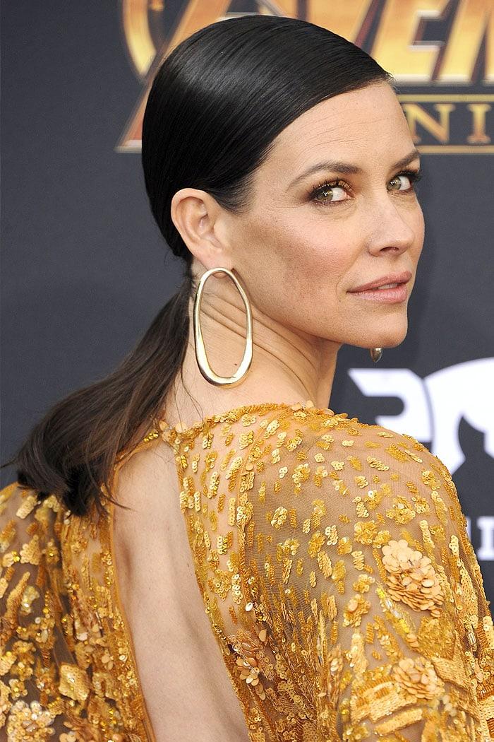 Evangeline Lilly wearing elongated, gold hoop earrings.