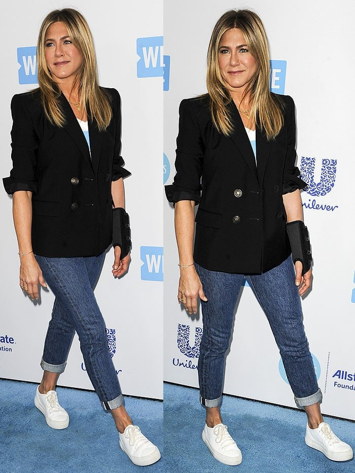 Jennifer Aniston wearing cuffed acid-wash jeans and white sneakers
