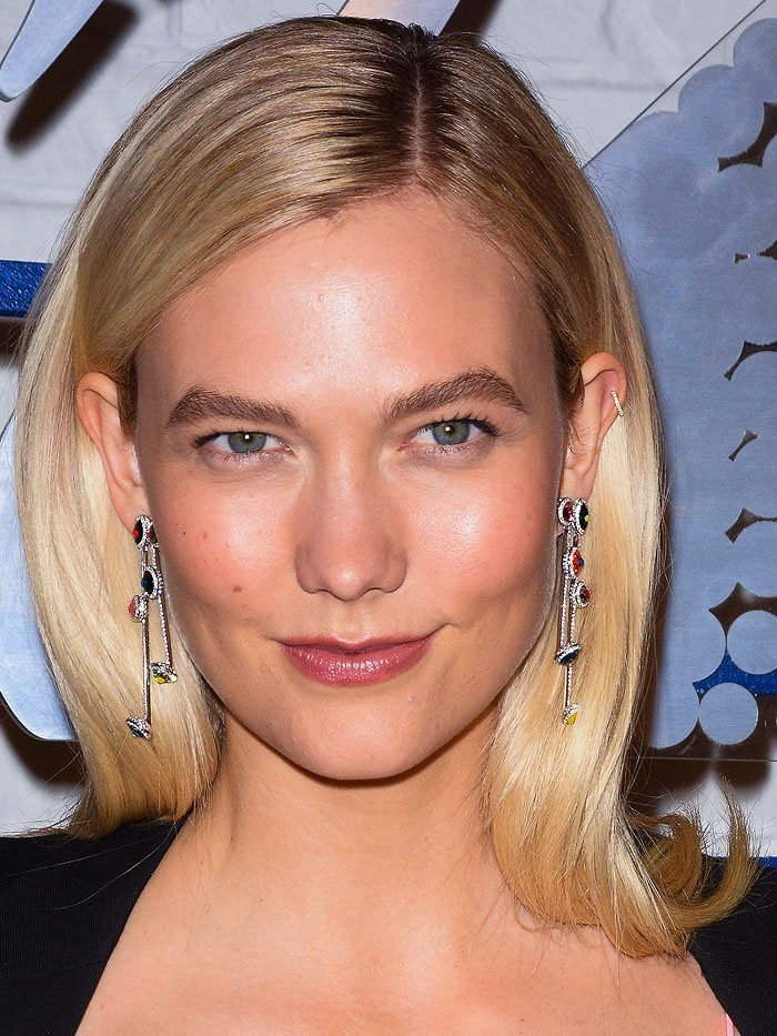 Karlie Kloss wearing Swarovski 'Luminous Fairy' clip earrings with multi-colored crystals and plated in rhodium.