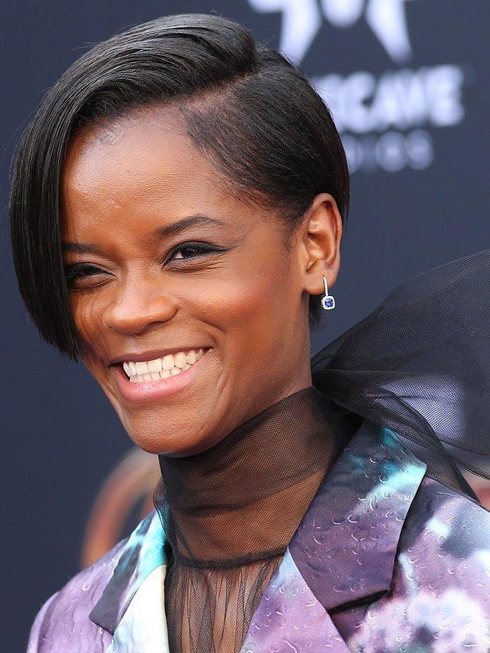 Letitia Wright wearing Norman Silverman Sapphire Earrings and an edgy, blunt short haircut.