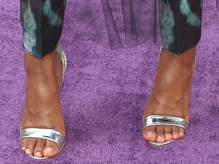 Closeup of Letitia Wright's custom silver Prada ankle-strap sandals with tiered heel cups.