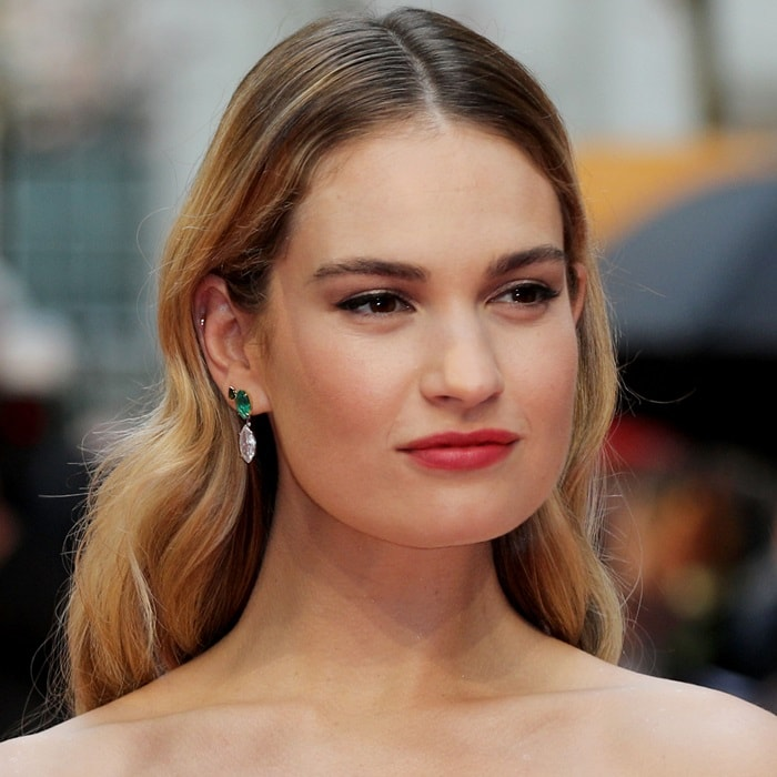 Lily James showing off herdiamond and emerald dropper earrings