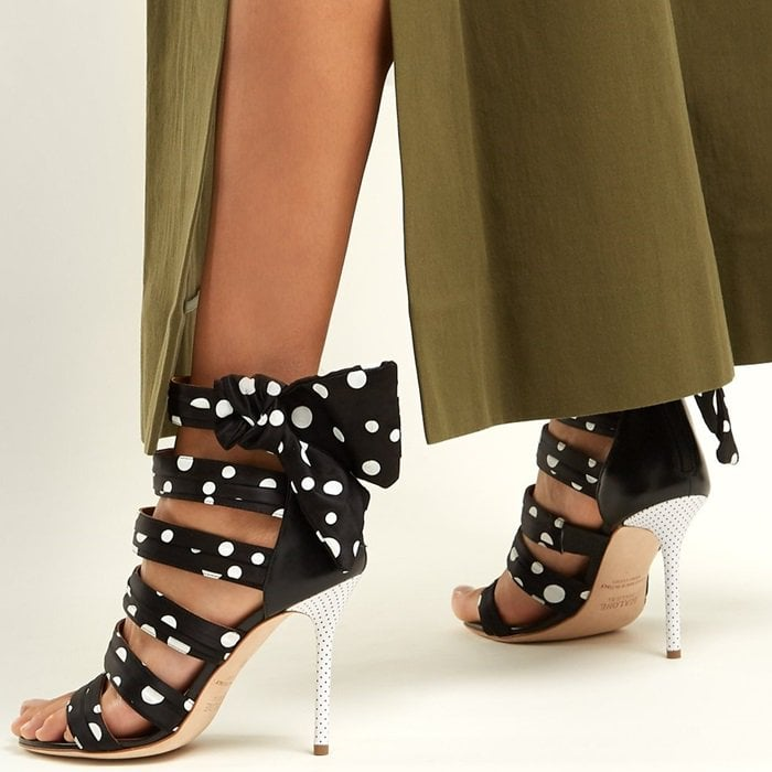 Graphic polka dots play out across the arched foot straps and side bows