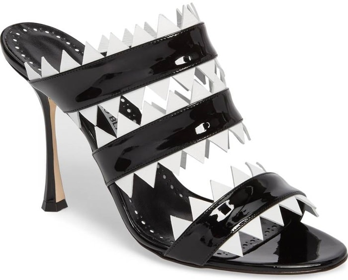 Glossy patent straps edged in geometric accents add to the fiercely stylish look of a sharp mule set on a flared stiletto heel.