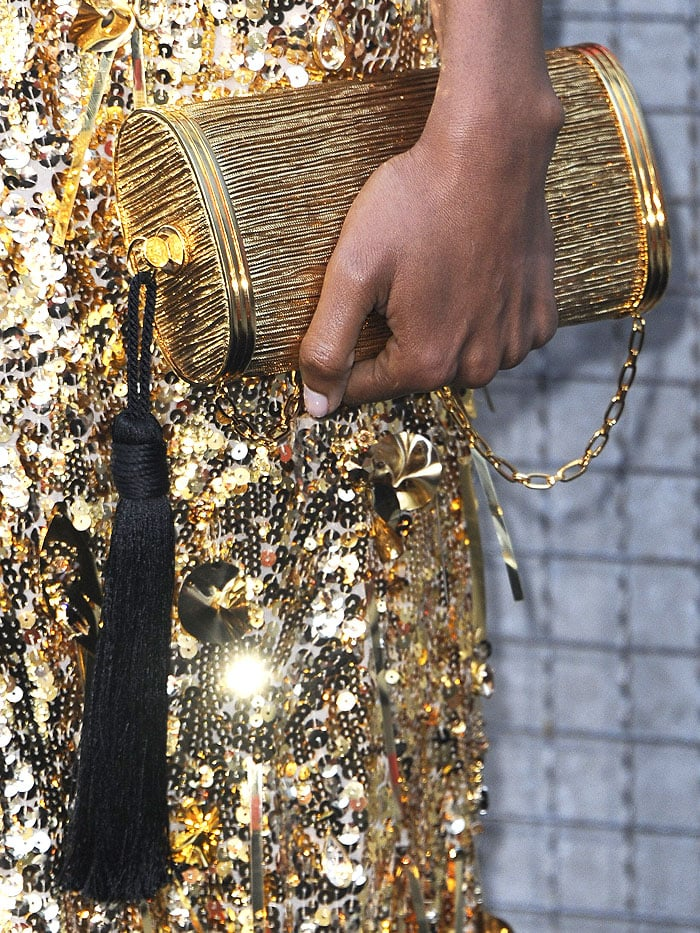 Details of Naomi Harris' Bienen-Davis gold tube clutch with black tassel detail.