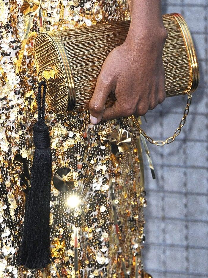 Details of Naomi Harris'Bienen-Davis gold tube clutch with black tassel detail.