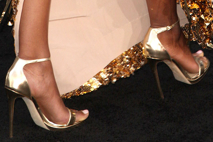 Naomie Harris with a slight toe overhang situation in her Jimmy Choo metallic-gold ankle-strap platform sandals.