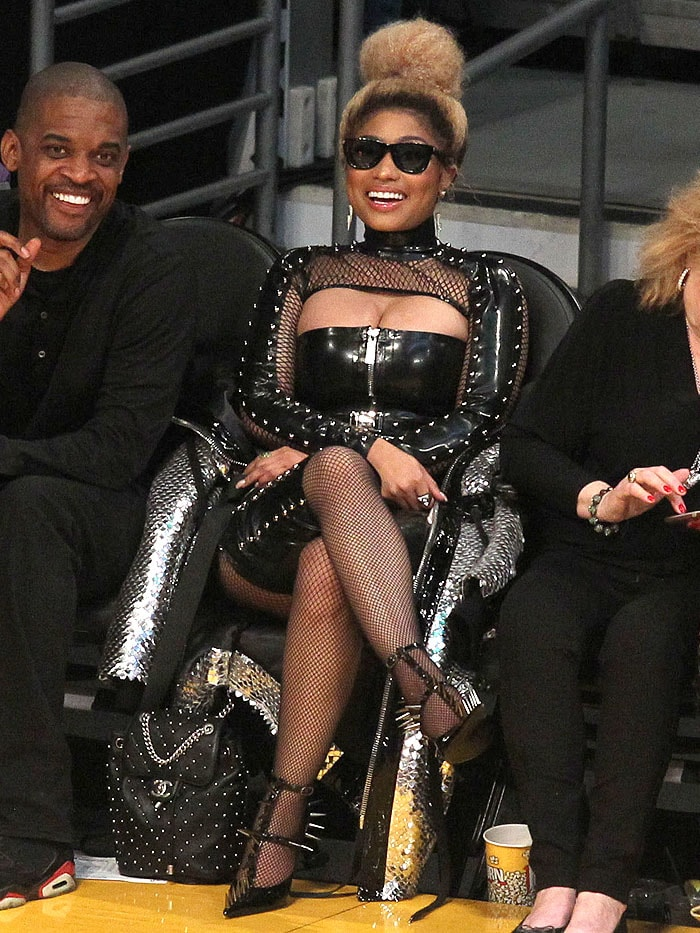 Nicki Minaj in leather, spikes, fishnets, and spiked pumps and carrying a Chanel studded leather backpack.