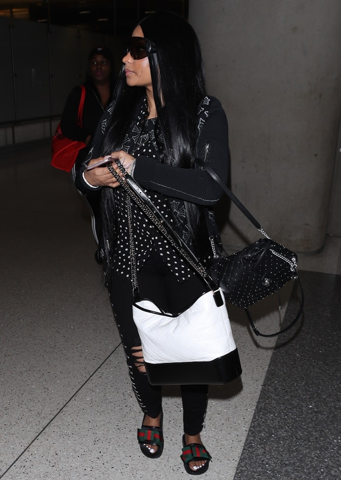 Nicki Minajin ripped black metal-embellished pants, a baggy polka dot blouse, and a pair of supersized sunglasses