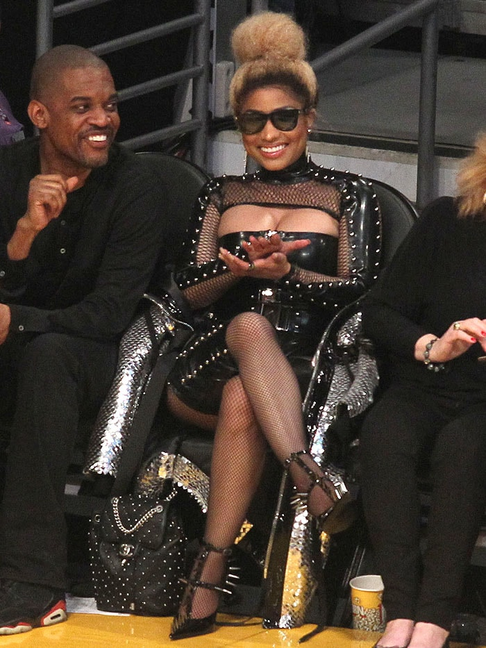 Nicki Minaj wearing a leather bodysuit, fishnets, spiked chaps, and spiked pumps.