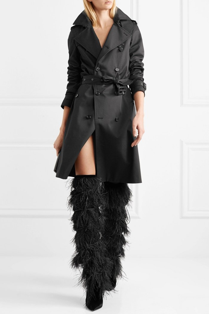 Model wearing a black 'Gabardine' trench coat and Yeti feather-trimmed suede over-the-knee boots
